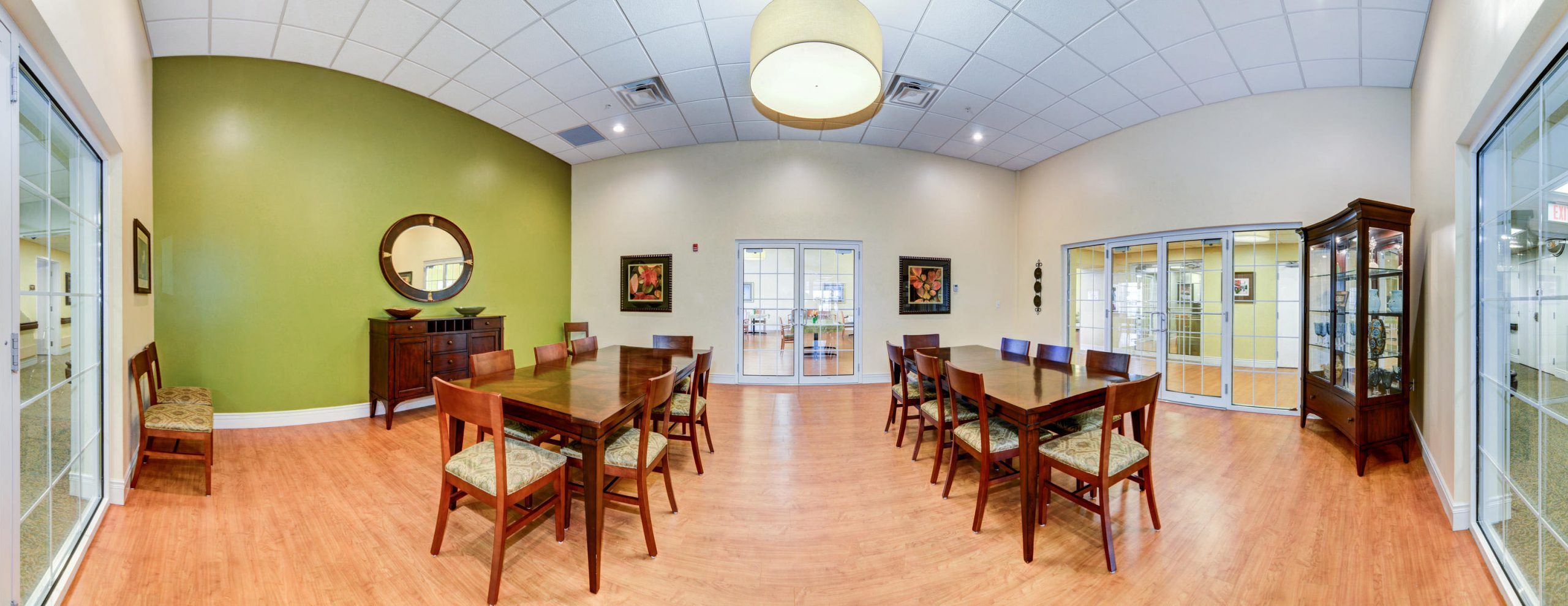 Panoramic view of Stonerise Morgantown gathering room with two large tables and seating