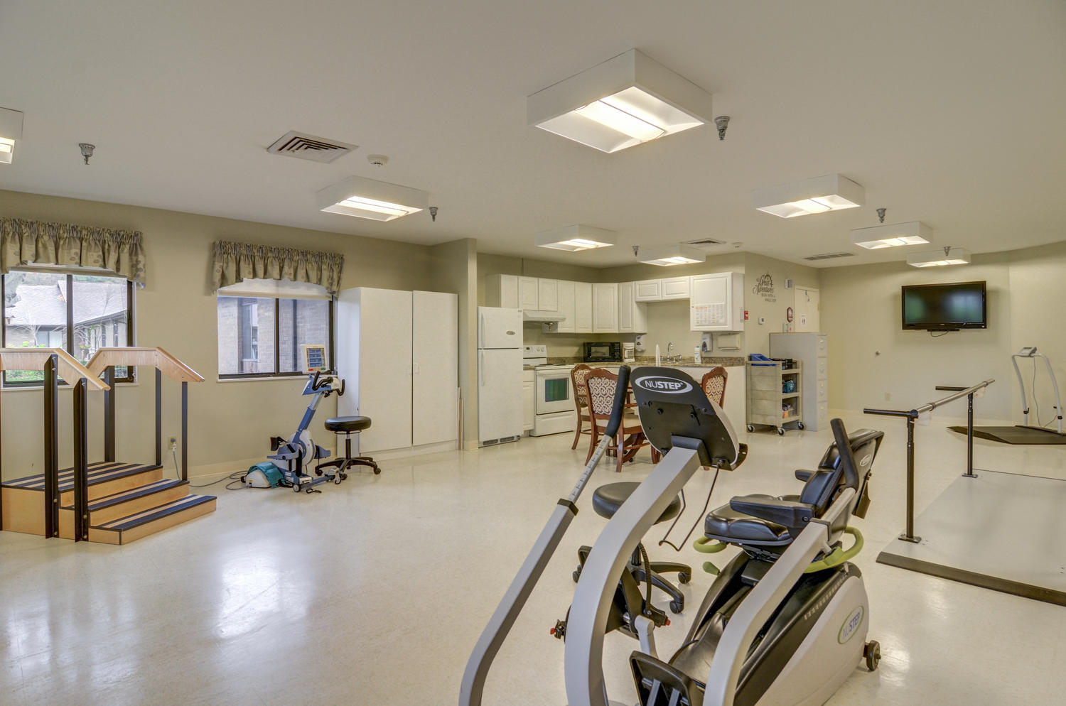 Stonerise Belmont Physical Therapy equipment with kitchen area and TV in the background