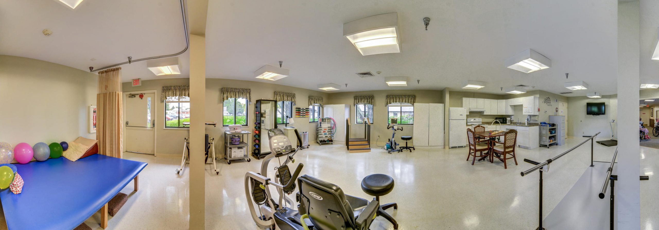 Panoramic view of Stonerise Belmont Therapy and Rehabilitation room with equipment and kitchen area
