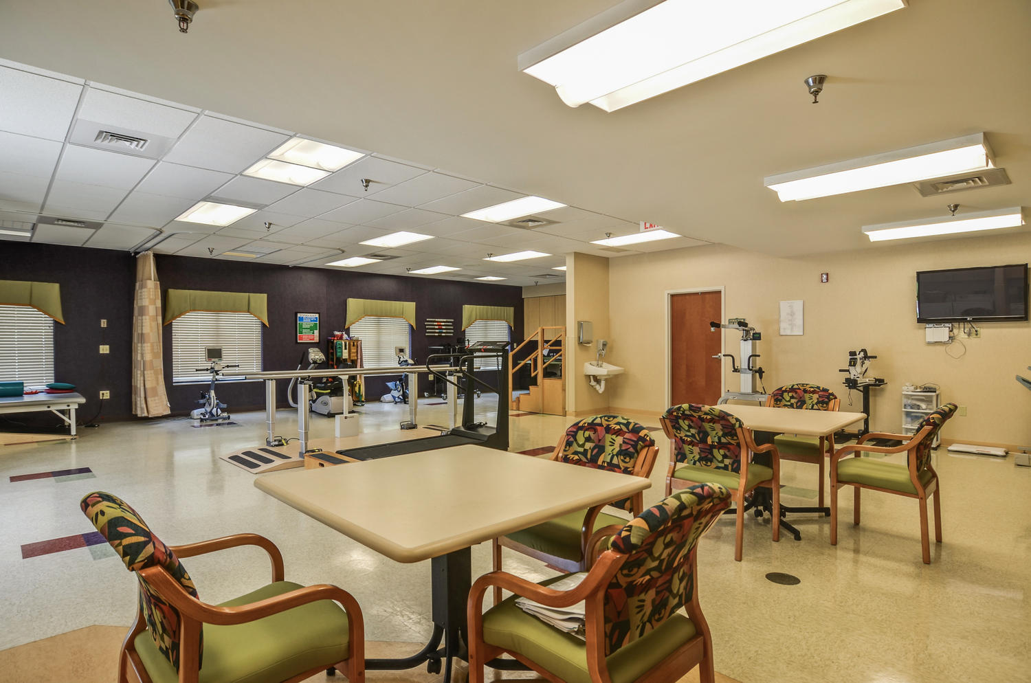Stonerise Clarksburg Therapy and Rehabilitation room with equipment, seating areas and TV