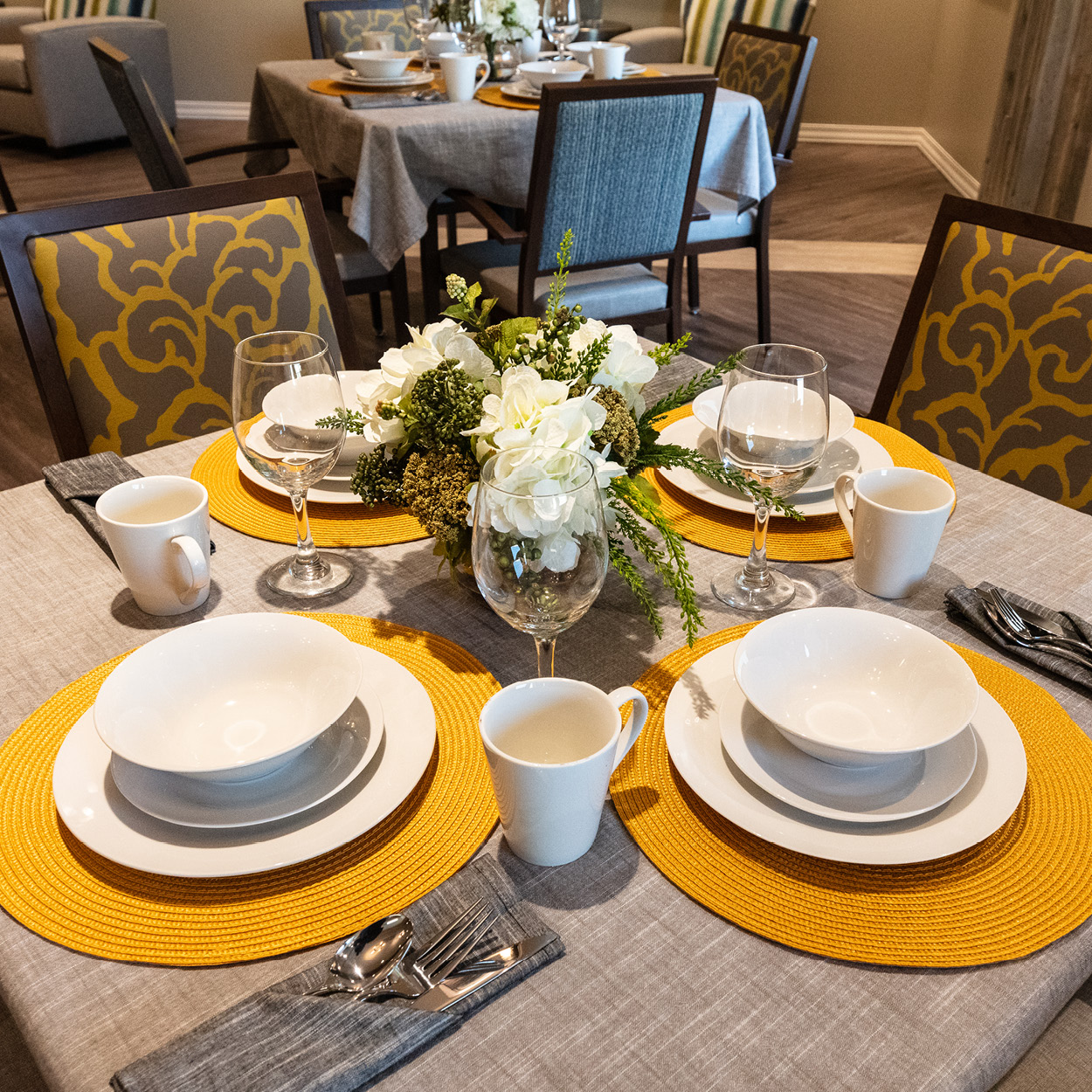 Stonerise Charleston dining table with place settings and floral centerpiece