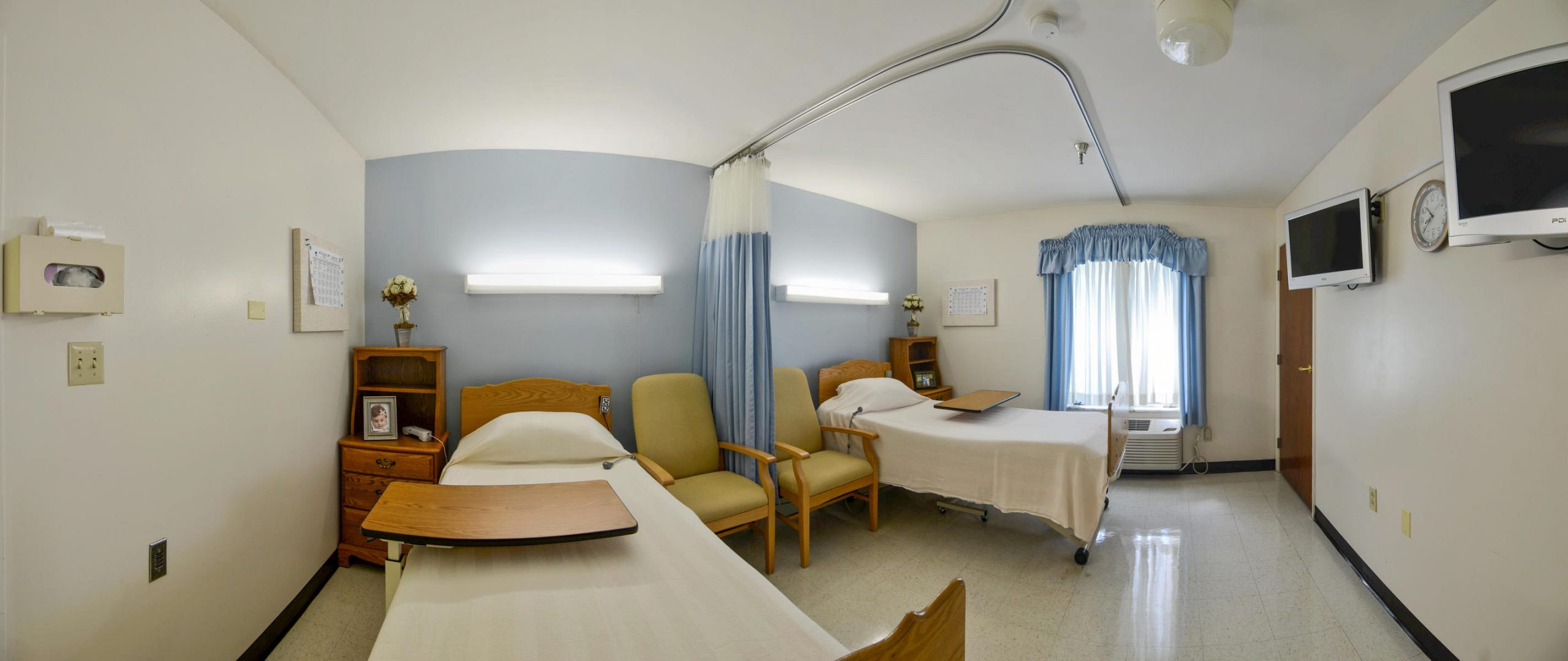 Panoramic view of Stonerise Clarksburg patient room with two beds and open curtain