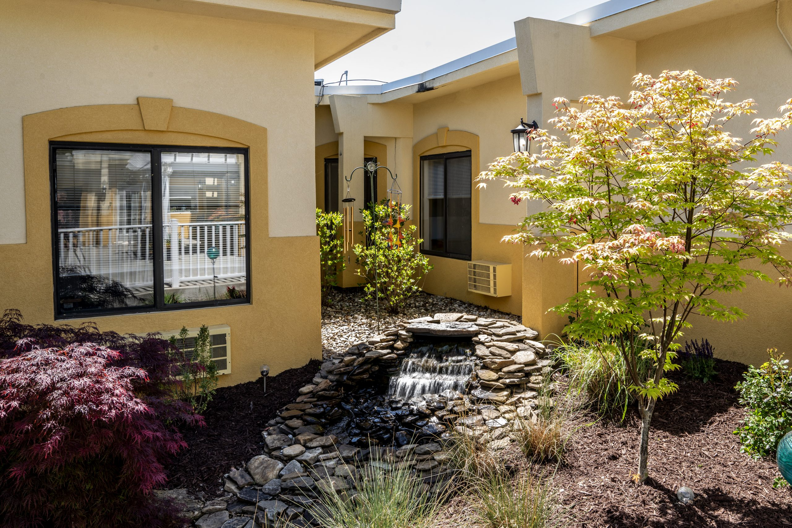 Courtyard area at Stonerise Parkersburg with small waterfall, wind chimes and trees