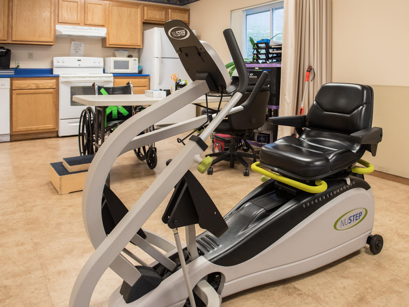 Exercise bike and other equipment in Stonerise Lewisburg Therapy and Rehabilitation room with view of kitchen area