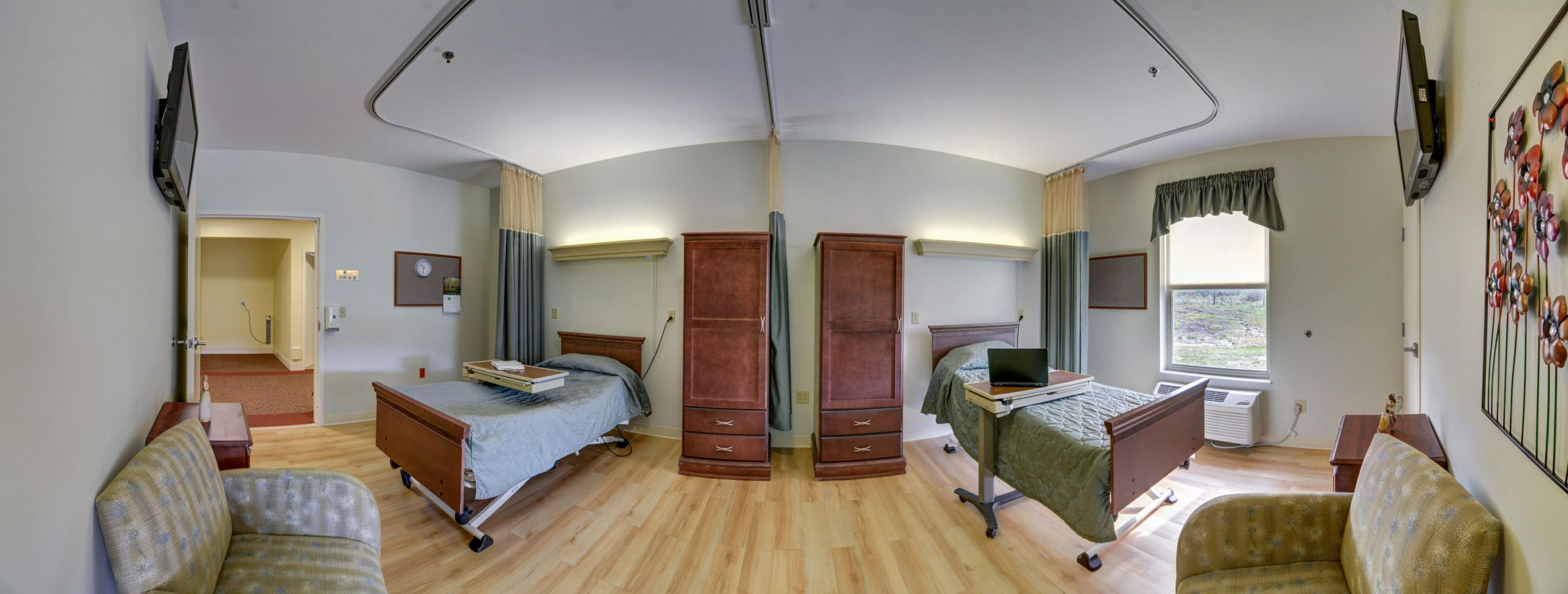 Panoramic view of Stonerise Lindside semiprivate patient room with two beds and two TVs