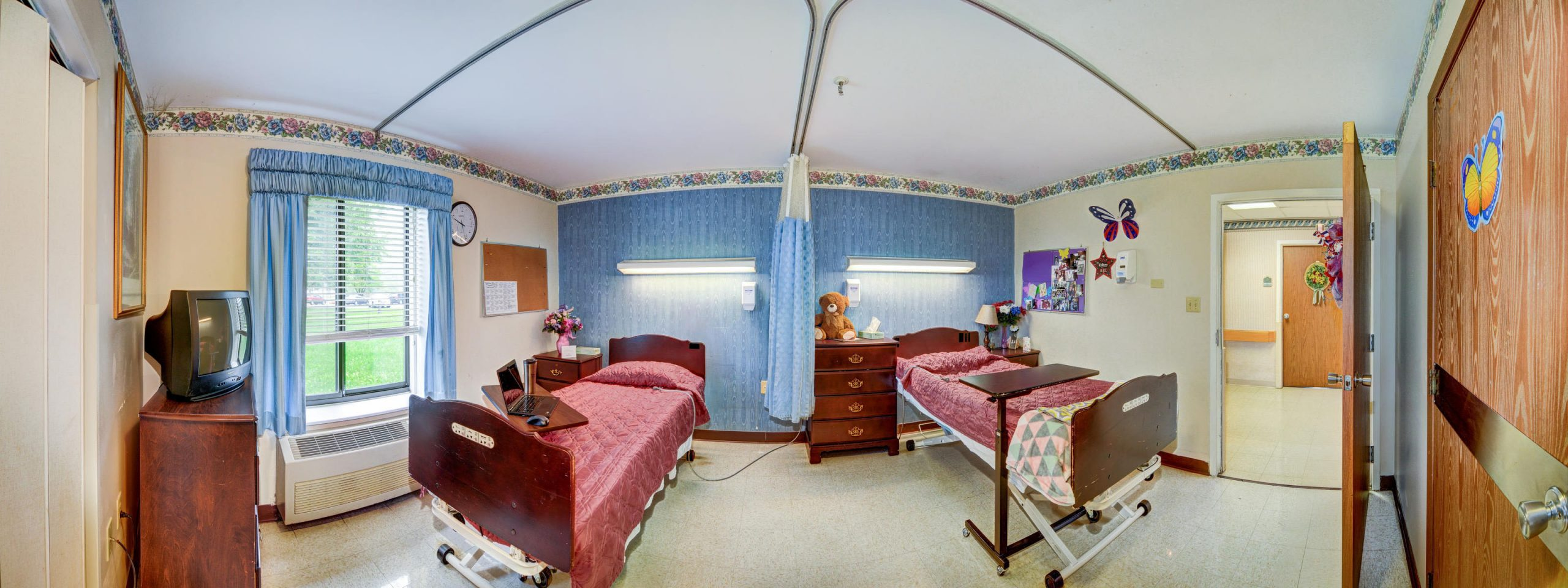 Panoramic view of Stonerise Keyser patient room with two beds and TV