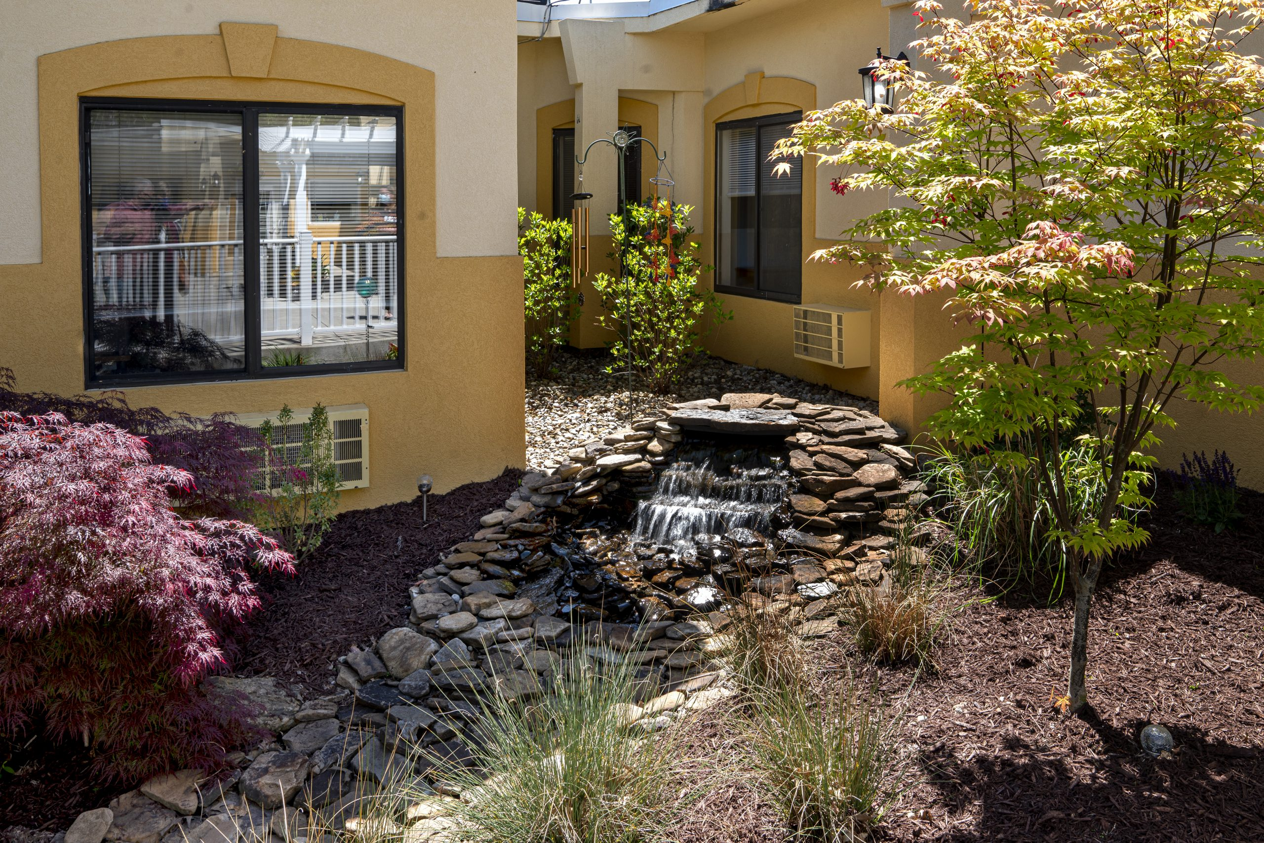 Courtyard area at Stonerise Parkersburg with small waterfall and colorful trees