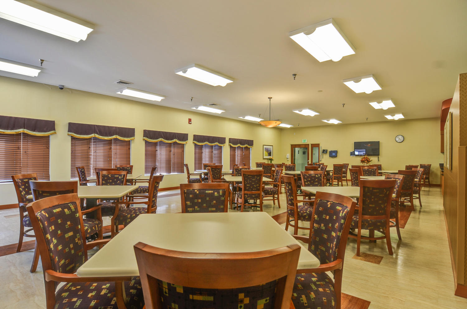 Stonerise Clarksburg dining room with TV, windows and patterned chairs