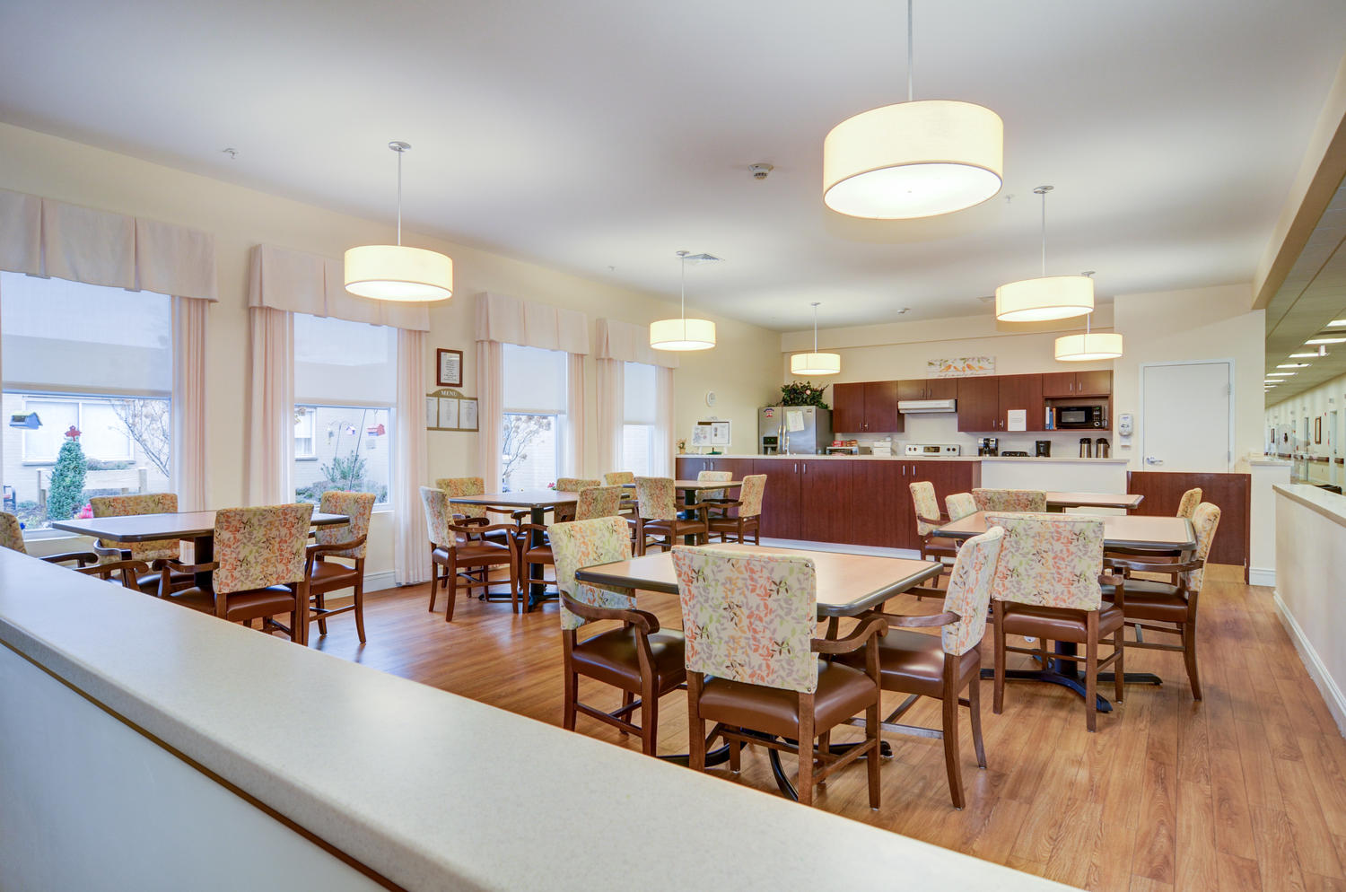Stonerise Morgantown Memory Care dining room with colorful chairs and kitchen area