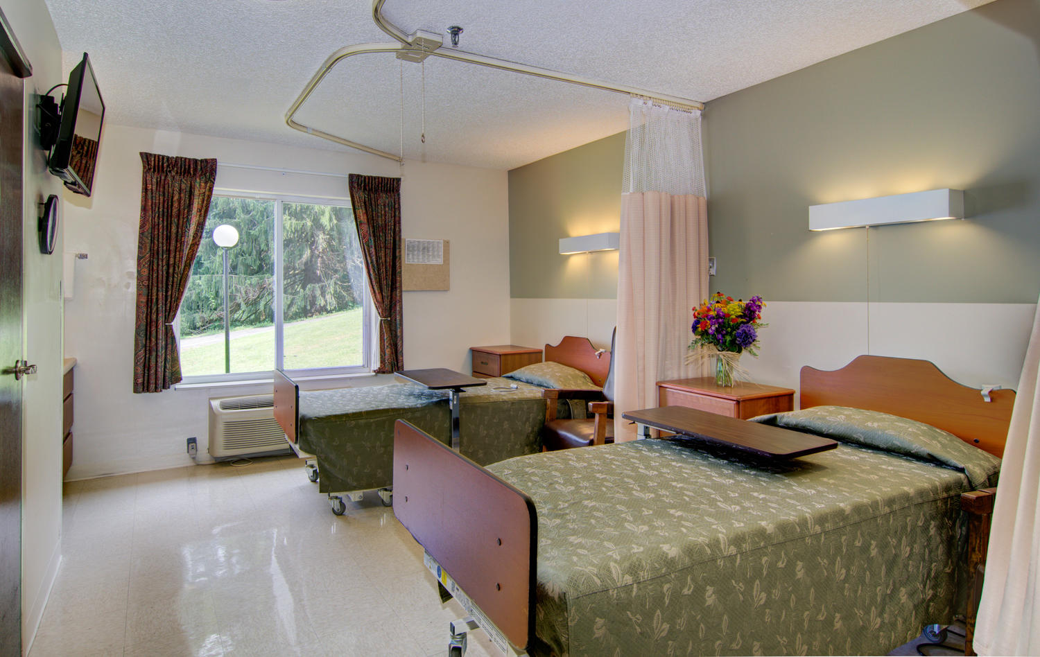 Stonerise Wellsburg patient room with two beds and flowers