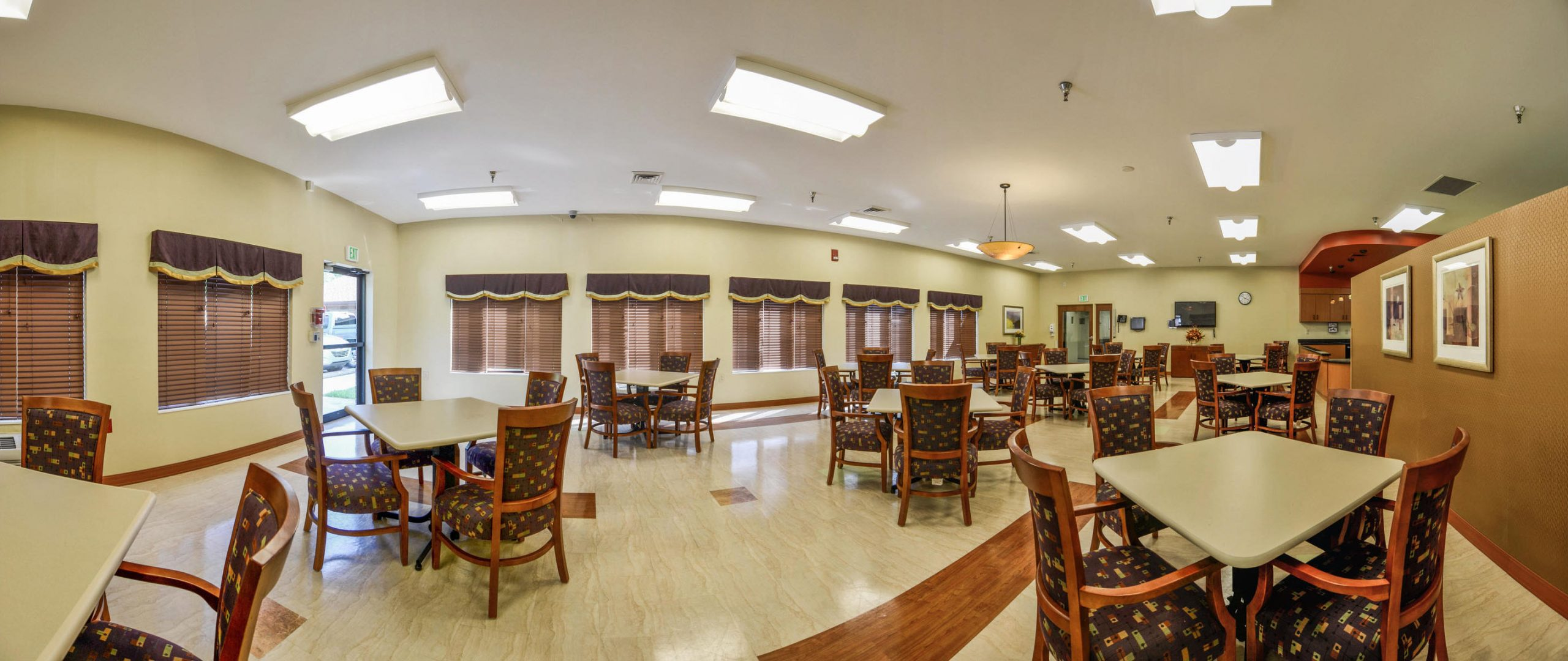 Panoramic view of Stonerise Clarksburg dining room with TV and windows