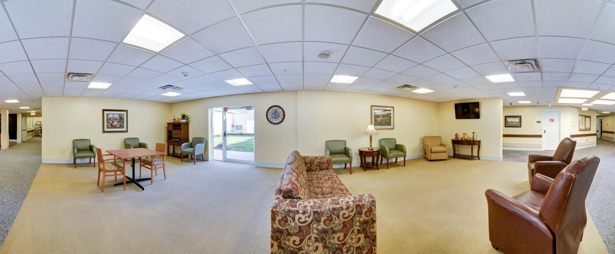 Panoramic view of Stonerise Morgantown sitting room with leather chairs and patterned sofa
