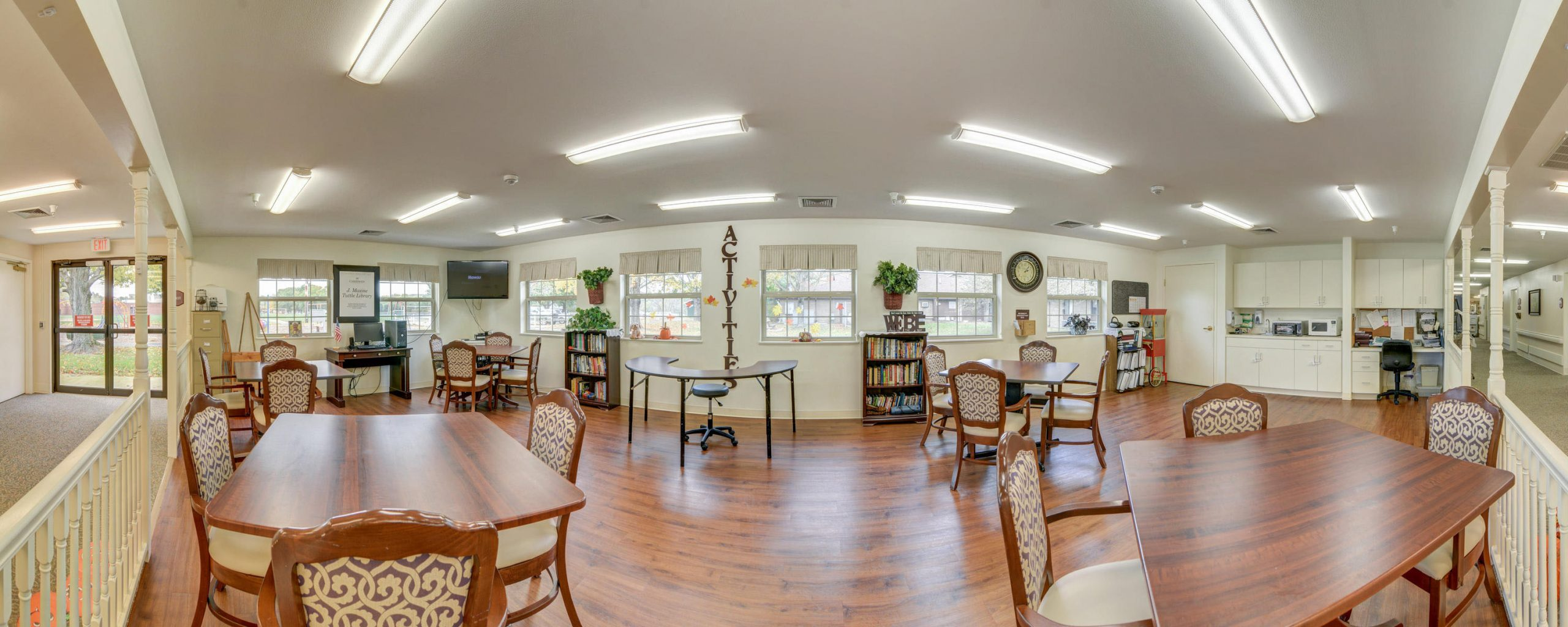 Panoramic view of Stonerise Belmont activities room with bookshelves, computer and TV