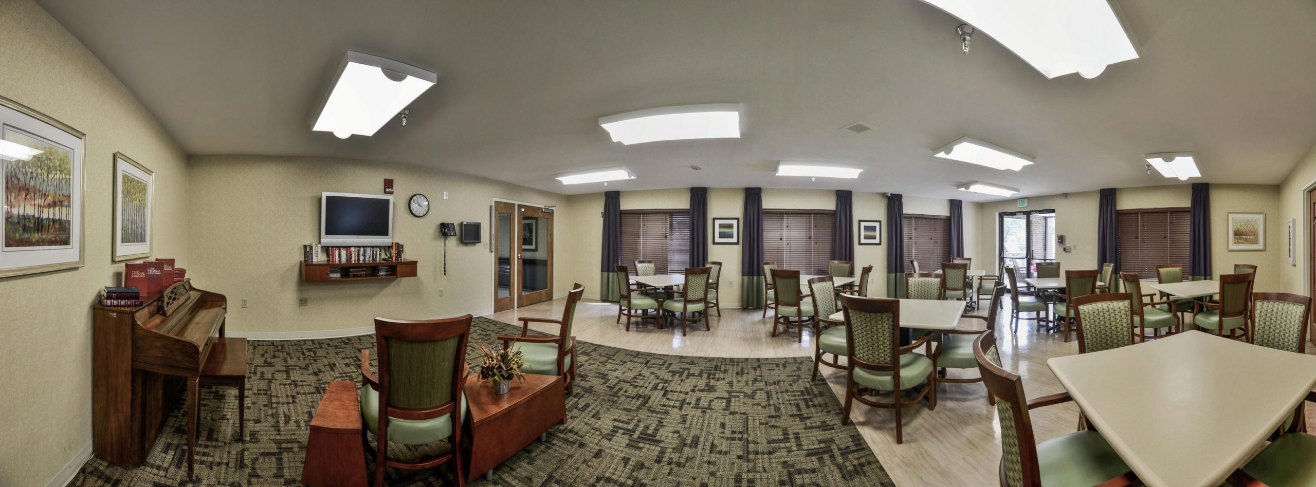Panoramic view of Stonerise Clarksburg activity room with TV, books and piano