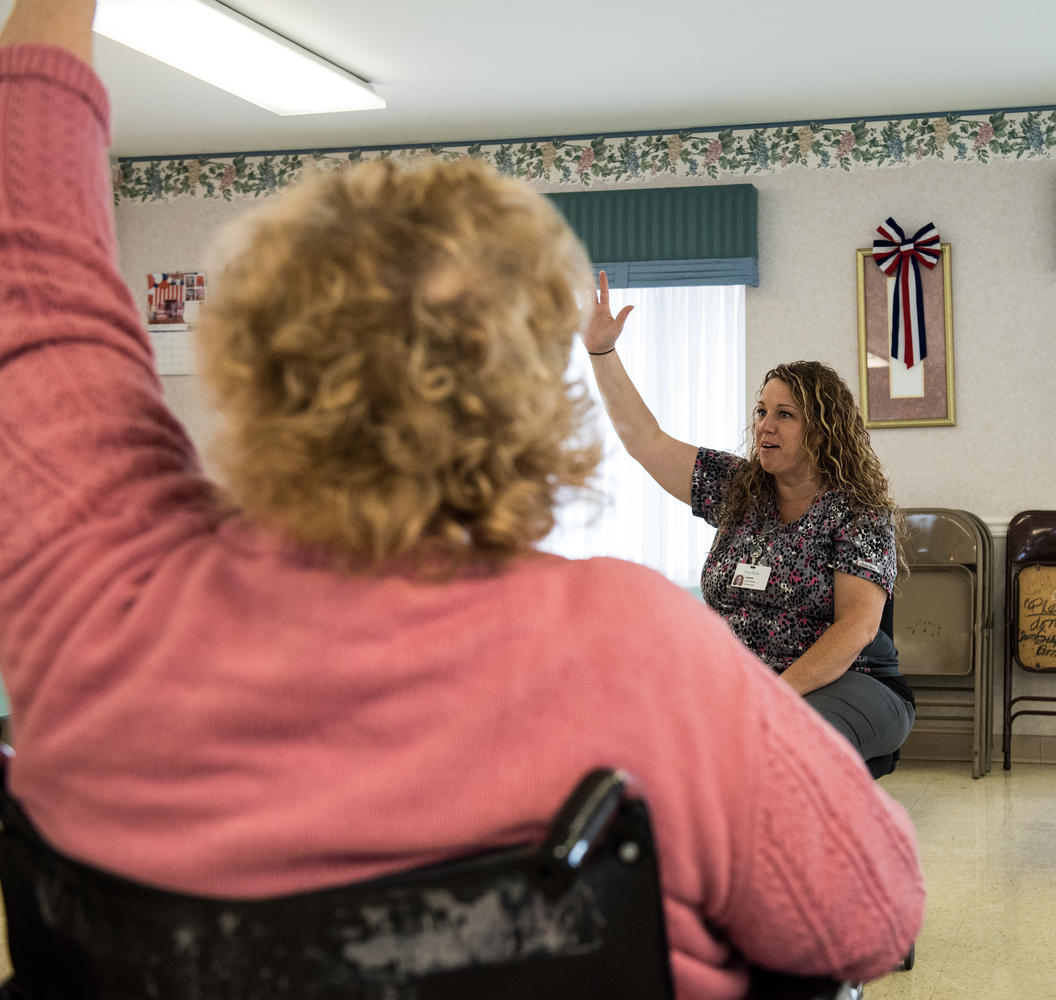 Stonerise Keyser team member and patient raise their hands during an exercise activity