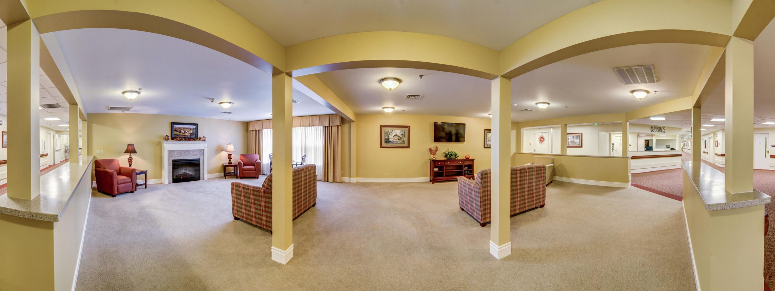 Panoramic view of Stonerise Lindside sitting room with fireplace, TV and sofas