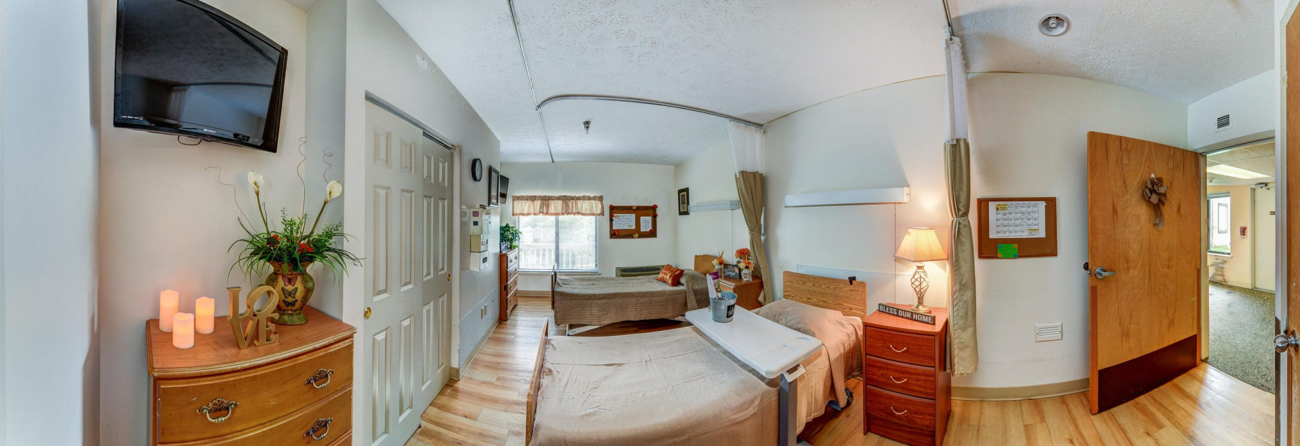 Panoramic view of Stonerise Parkersburg patient room with two beds and TV