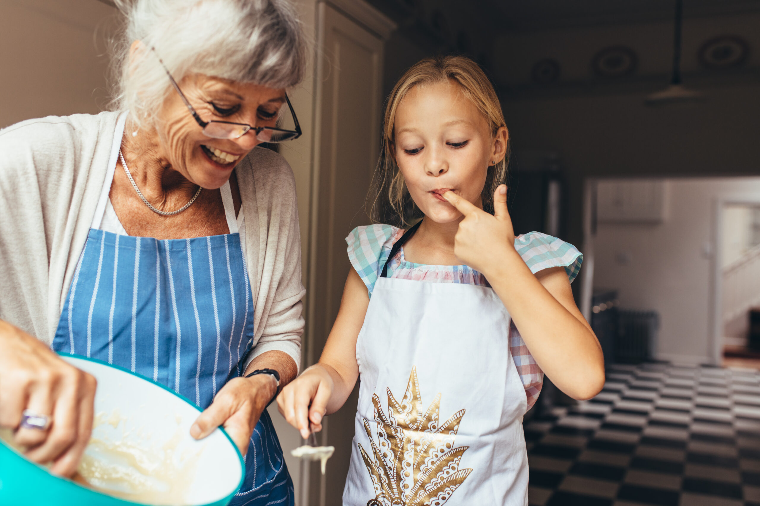 Elderly woman and child baking in kitchen