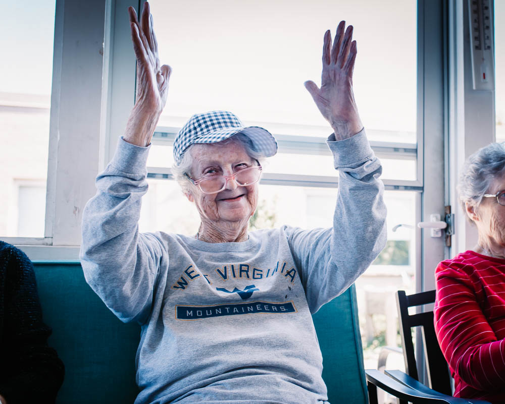 Elderly woman cheering in nursing home in West Virginia Mountaineers sweatshirt