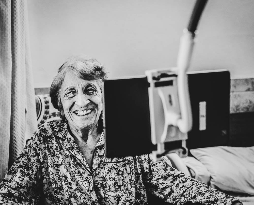Elderly woman smiling during virtual televisit in Stonerise skilled nursing home and transitional care facility