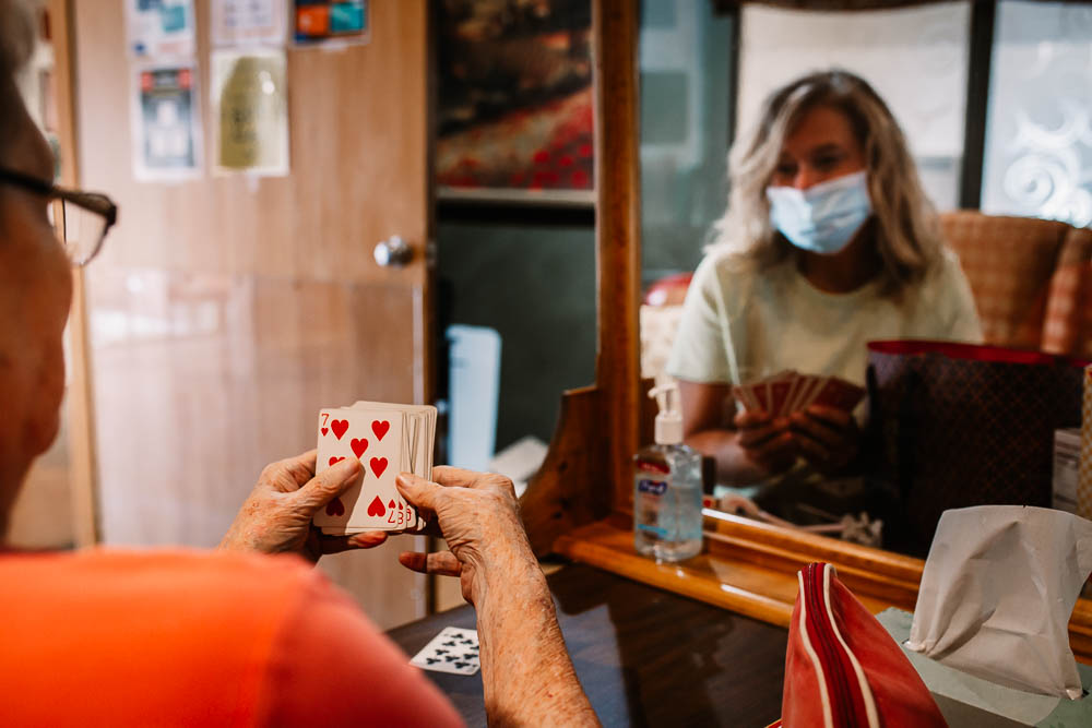 Patient and visitor playing cards in a Stonerise skilled nursing home and transitional care facility