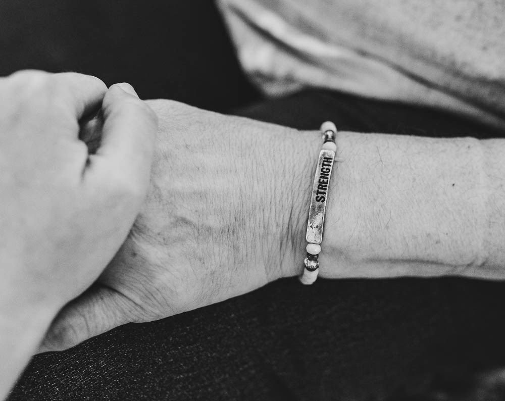 People holding hands with strength bracelet