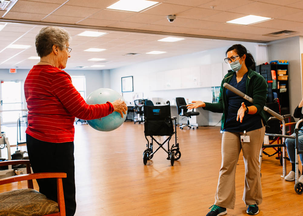 Stonerise healthcare worker and elderly patient doing physical therapy in gym