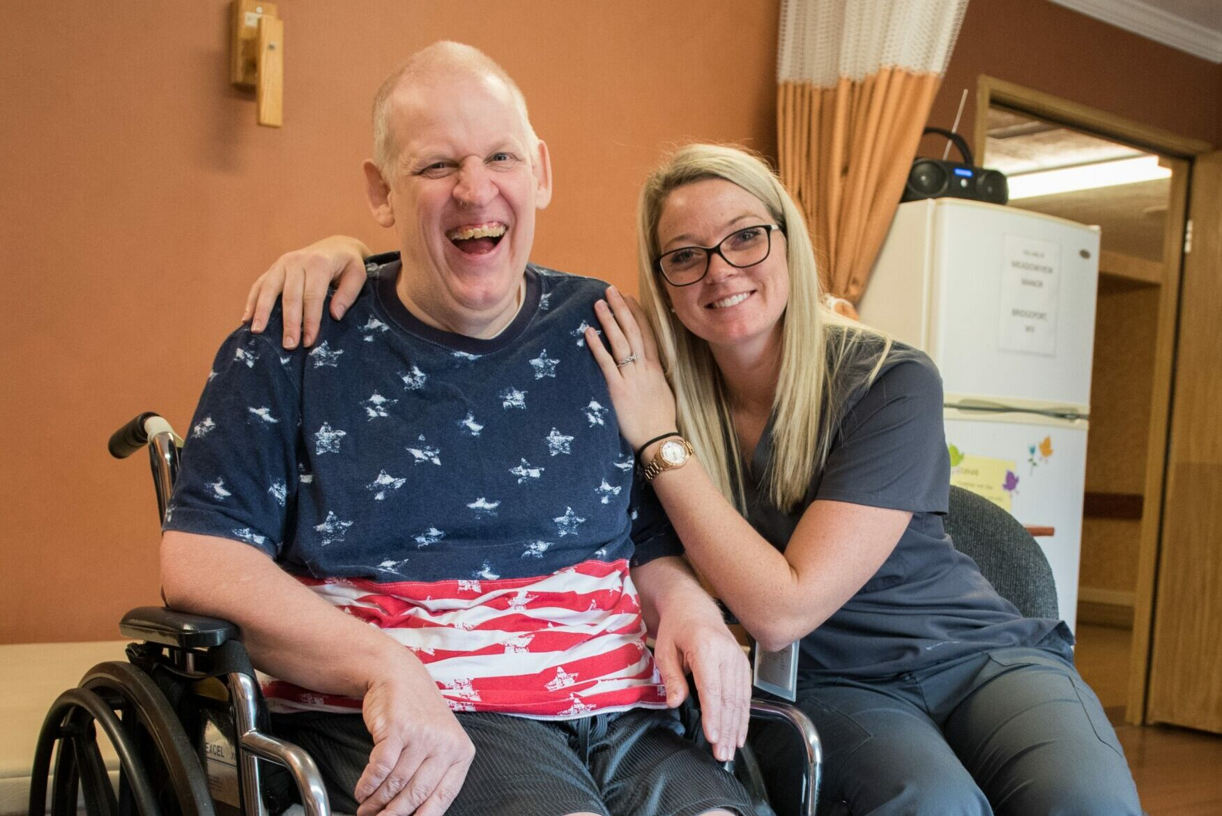 Stonerise healthcare worker and patient in wheelchair laughing at Stonerise Bridgeport skilled nursing home and transitional care facility