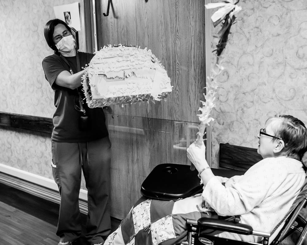 Stonerise healthcare worker and patient playing with pinata in nursing home