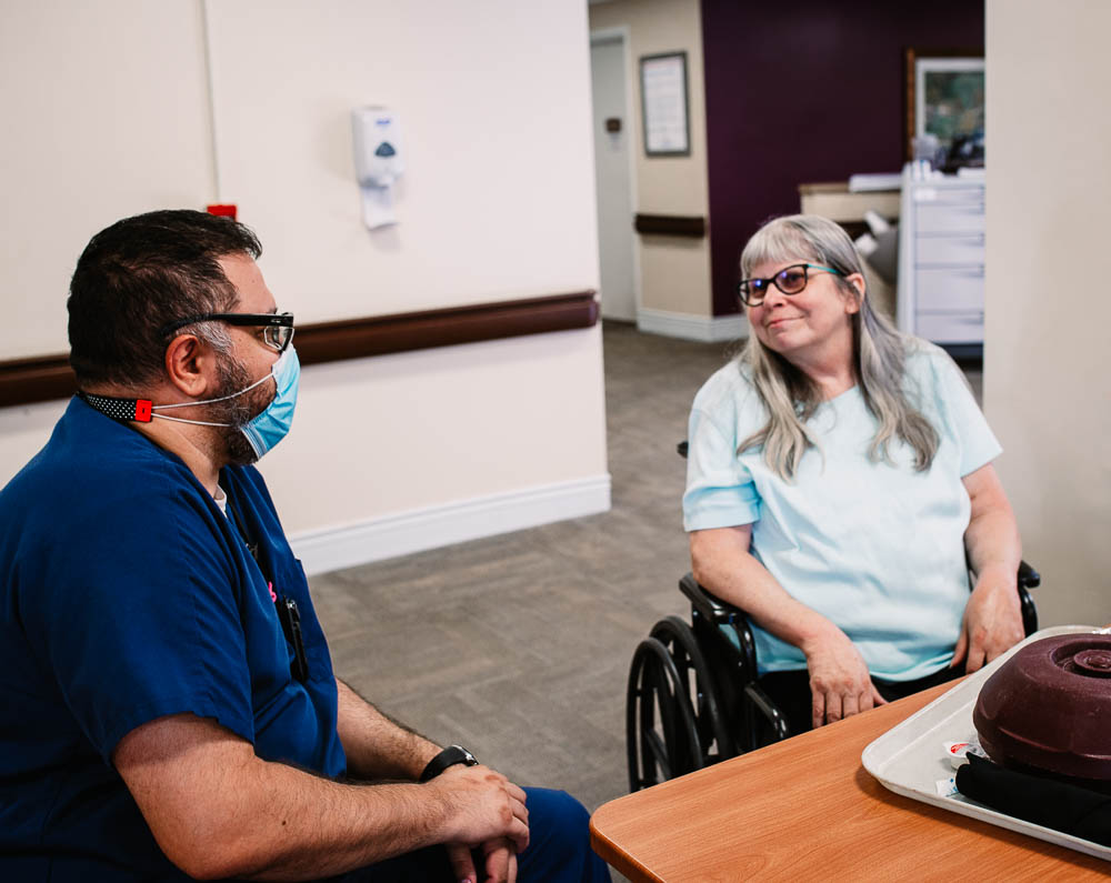 Stonerise healthcare worker and wheelchair patient smiling in skilled nursing home and transitional care facility