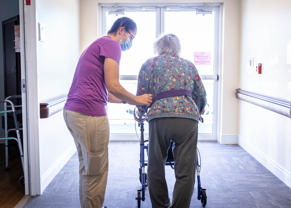 Stonerise healthcare worker helping patient with walker
