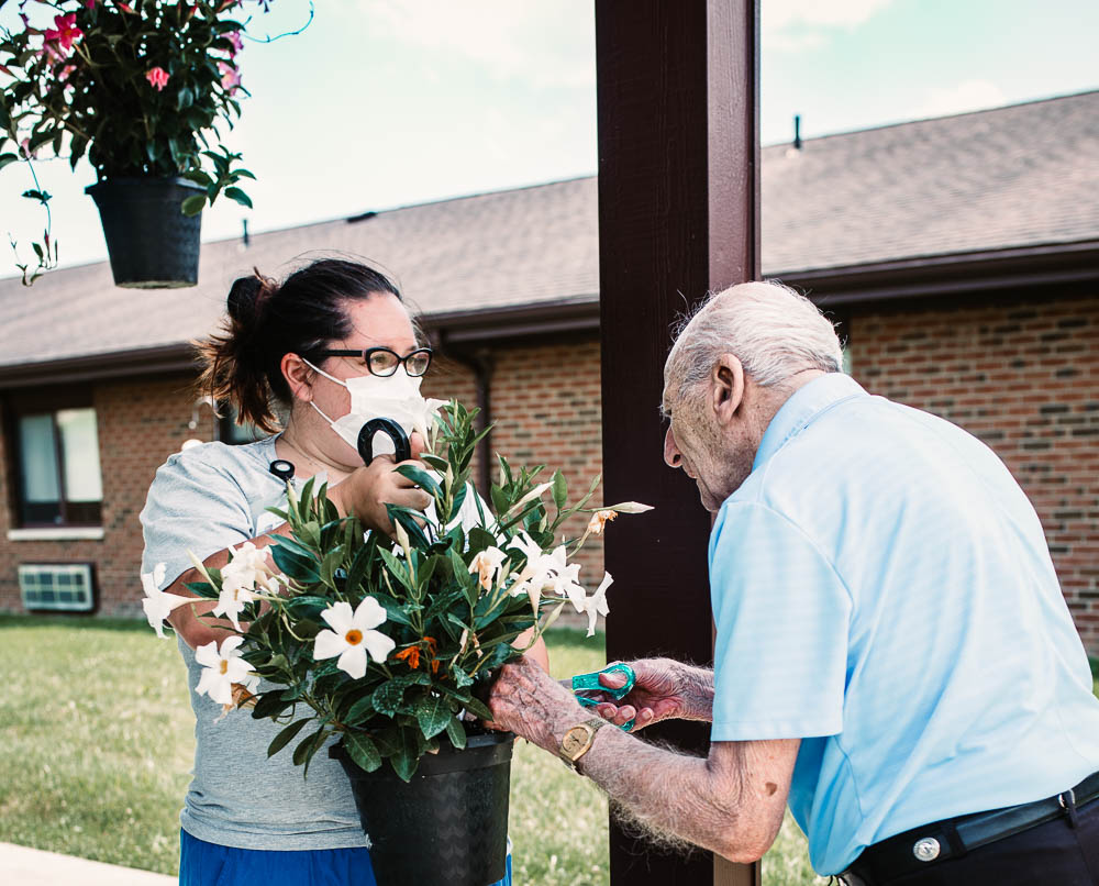 Stonerise healthcare worker wearing mask gardening with elderly patient outside of skilled nursing home and transitional care facility